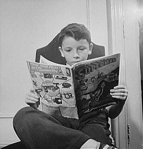 photo of boy reading a comic book