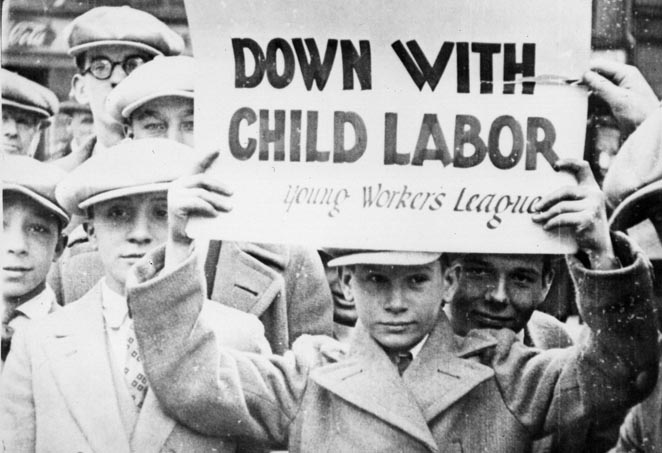 Group of boys. Boy in center holding up sign  reading down with child labor young workers league