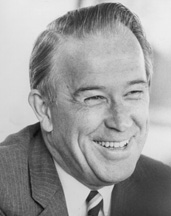 Black and white profile image of older white man smiling and looking away from camera.