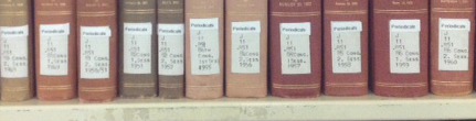 The spines of about a dozen books with call number labels on a bookshelf