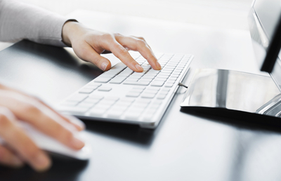 Image of hands using a computer keyboard and mouse