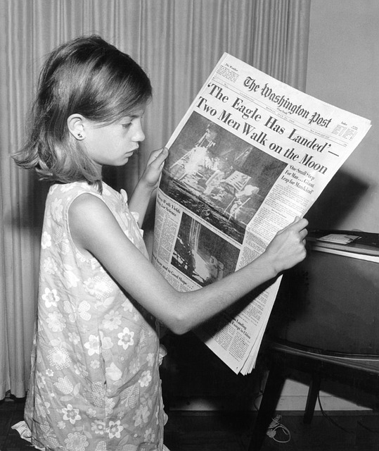 Young Girl reading a newspaper about Apollo 11