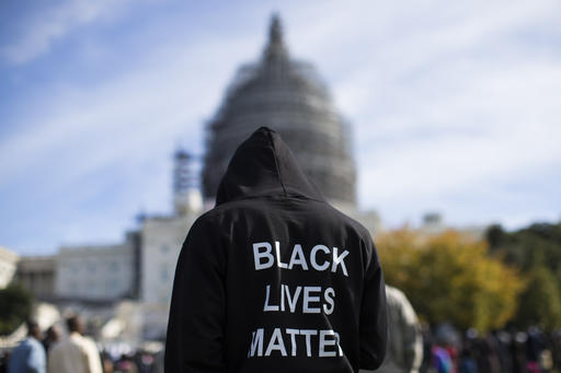 """In this Oct. 10, 2015 file photo, a man wears a hoodie which reads, """"Black Lives Matter"""" as stands on the lawn of the Capitol building on Capitol Hill in Washington during a rally to mark the 20th anniversary of the Million Man March. A new poll shows a majority of American young adults, including white youth, support the Black Lives Matter movement. The support from young white adults is an increase from the beginning of the summer and the first time in the poll a majority of black, white, Hispanic and Asian young adults expressed support for the Black Lives Matter movement. (AP Photo/Evan Vucci, File)"""