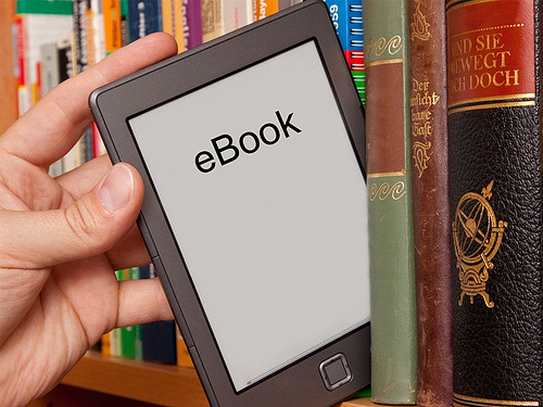 hand pulling ebook reader off a print bookshelf