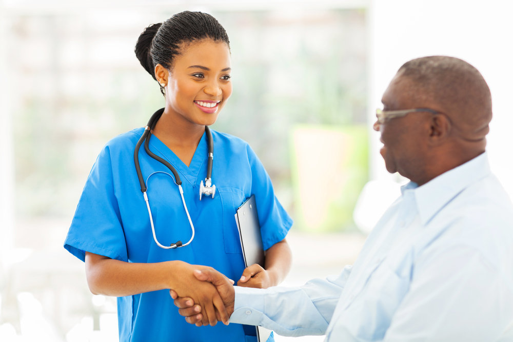 Woman in scrubs and wearing a stethoscope shakes hands with an older man.