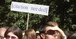 "Person holding a sign reading ""citation needed"""