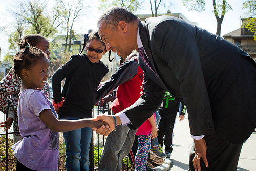 Middle-aged man in suit shaking hands with a little girl.