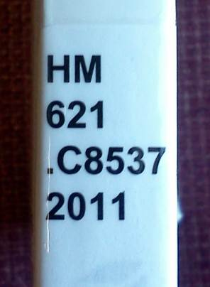 A close-up picture of the spine of a book. There is a label with the book's call number arranged in a vertical column with four lines of alternating letters and numbers