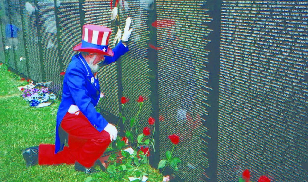 Blevins as Uncle Sam kneeling at the Vietnam Memorial replica