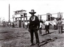 A black cowboy poses at a 1920s rodeo.