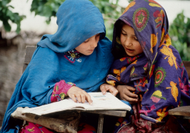 Girls study at an outdoor school in an Afghan refugee camp. Pakistan.