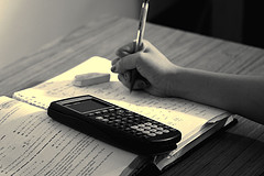 Student studying with textbook, pencil, eraser, and graphing calculator