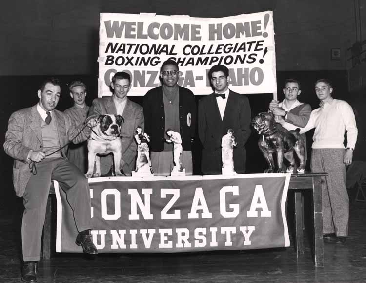 Item 115: National Collegiate Boxing Champions: Coach Joey August, Jim Reilly, Carl Maxey, and Eli Thomas with mascot, 1950