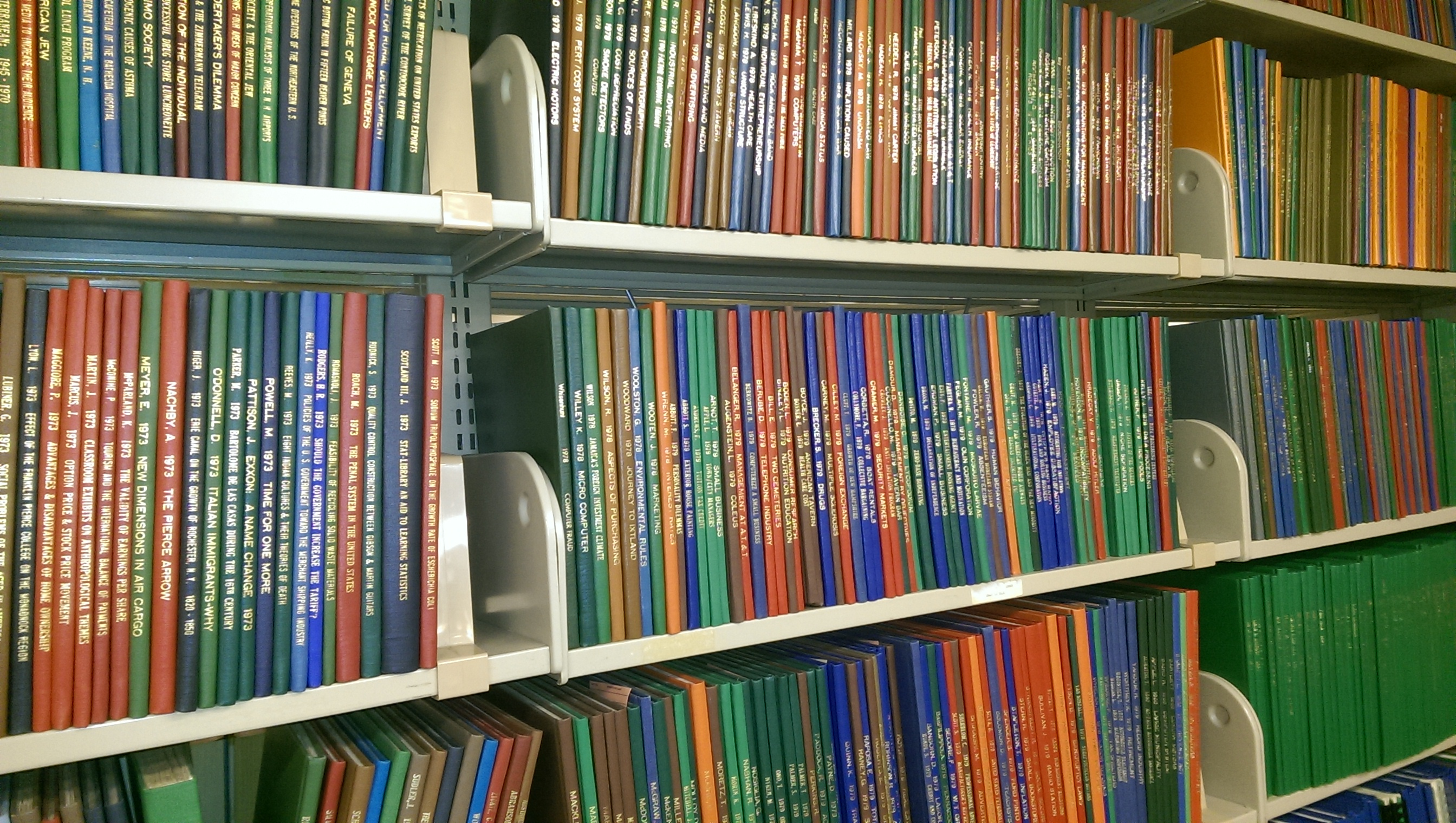 Bound dissertations of various colors line shelves.