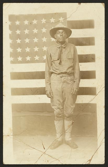 [World War I soldier with American flag in background]