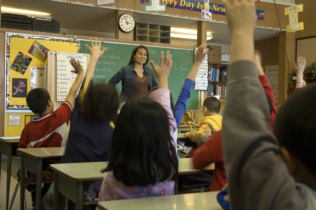 Photo of teacher standing in front of a class with students raising their hands