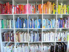 photograph of bookshelves with books organized in a rainbow of colors