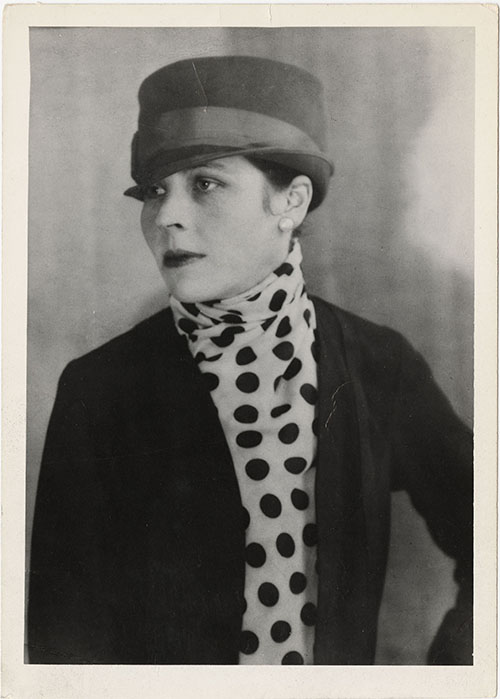 A portrait of Djuna Barnes wearing a hat and polka-dot ascot, taken in Paris, France, circa 1921-1922.