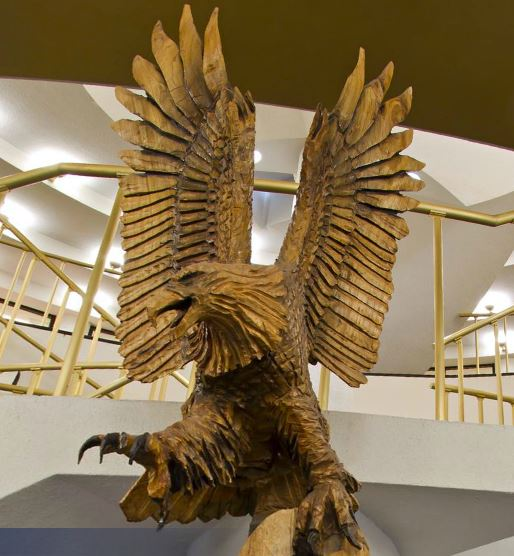 A large wooden carving of an American eagle that is located in the ORU Library