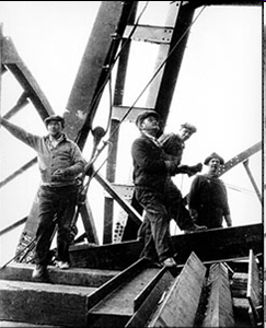 Four men standing on beams from a construction project.