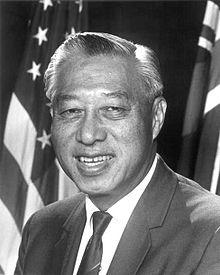Portrait of Hiram Fong posed in front of an American flag