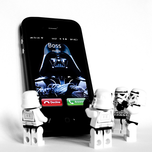 Darth Vadar Calling; Lego pieces standing around a giant smartphone with Darth Vader's image