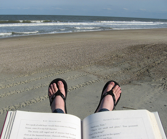 Image: a tranquil beach with a person's feet and an open book in the foreground