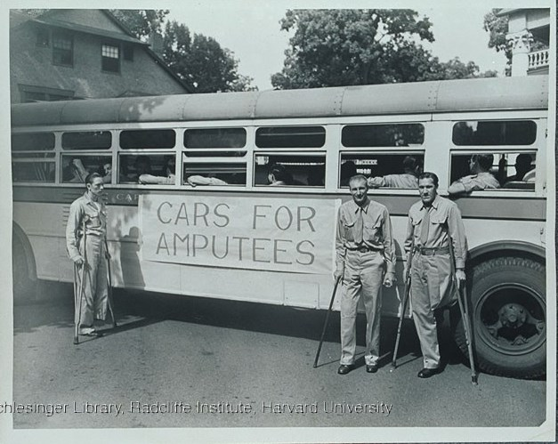 "Injured veterans standing outside in front of a bus which bears a banner ""Cars for amputees"". From Edith Nourse Rogers Papers MC 196."