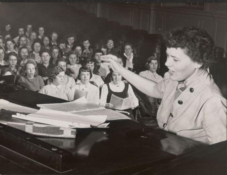 Victoria Merrylees Glaser conducts a choir, ca. 1956.