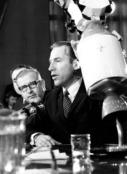 A black and white photo of two men behind a table. One gestures to a model of the Apollo spacecraft.