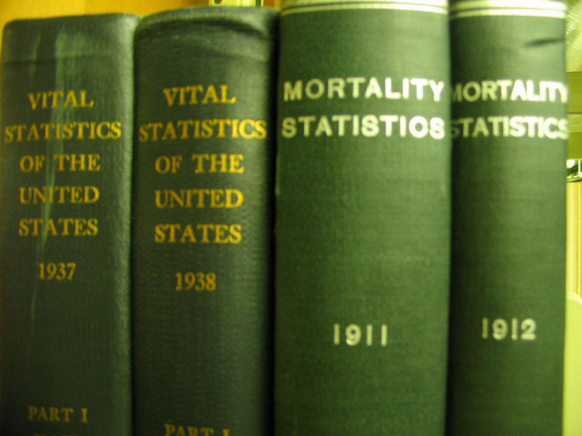 "a close up on a group of green bound books. the spines identify them as belonging to the series ""United States Vital Statistics"" and ""Mortality Statistics"""