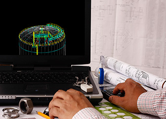 Laptop computer with circular CAD drawing on a desk with blueprints and other drawer tools near by.