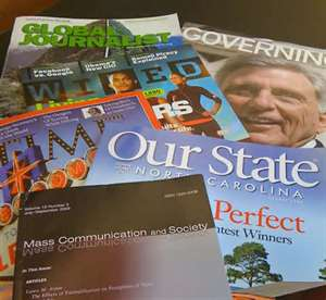 Multiple magazines scattered on a table.
