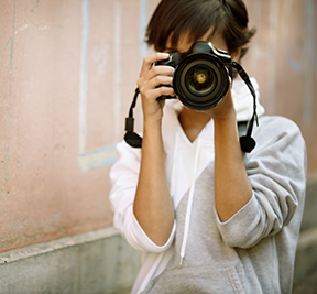 Photographer holding a DSLR camera to their face to take a photo.