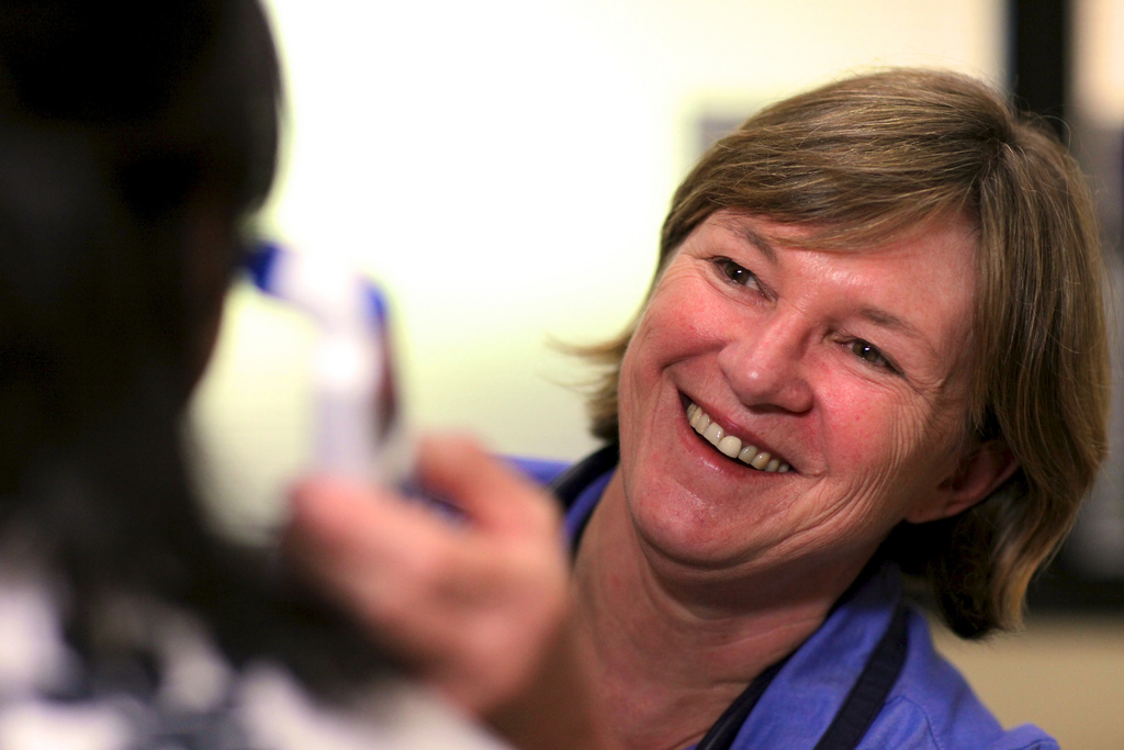 Smiling female nurse takes the temperature of a patient using an ear thermometer