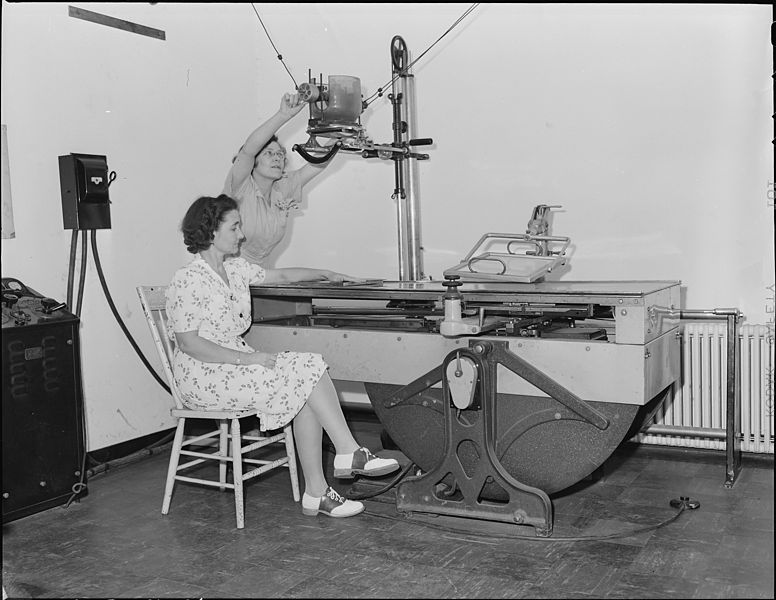 Vintage image of a woman sitting in a chair having her arm x-rayed by a female radiology technician.