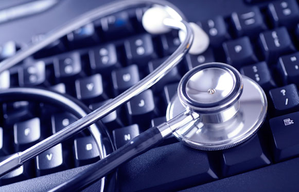 Stethoscope laying on top of a keyboard.