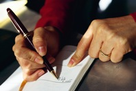 Picture of someone writing with a pen
