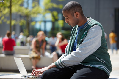 student using laptop out of doors