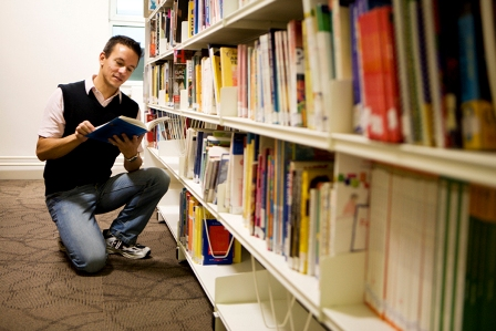 Student browsing the library shelves