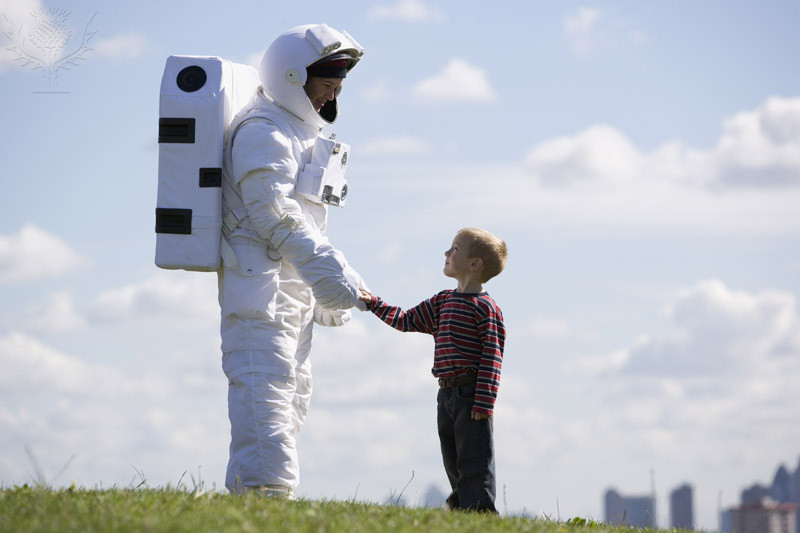 astronaut shaking the hand of a small boy