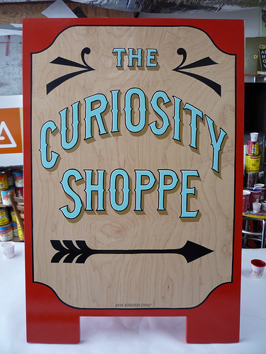 "Sandwich board with phrase ""the curiosity shoppe"" on it"