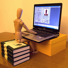 wooden artist's  model sitting on books looking at computer