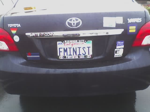 Back bumper of car with rainbow and equality stickers, and license plate reading FMINIST