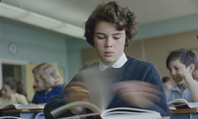 Girl sitting at desk flipping through textbook pages at Putnam School