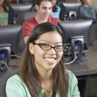 student with glasses at front of class