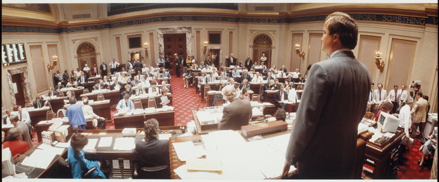 Members of the Minnesota House of Representatives meeting in the Senate Chambers