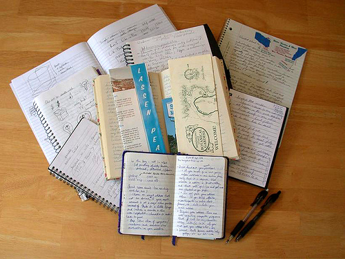 open notebooks containing handwritten notes and drawings stacked on top of one another