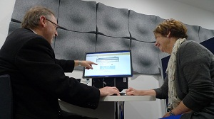 Librarian assisting a patron search the catalogue