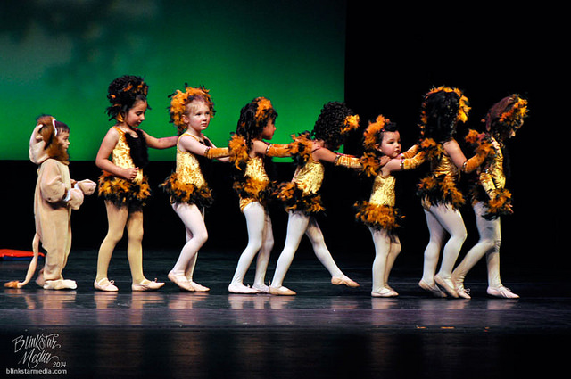 Children's dance group on stage in lion costumes